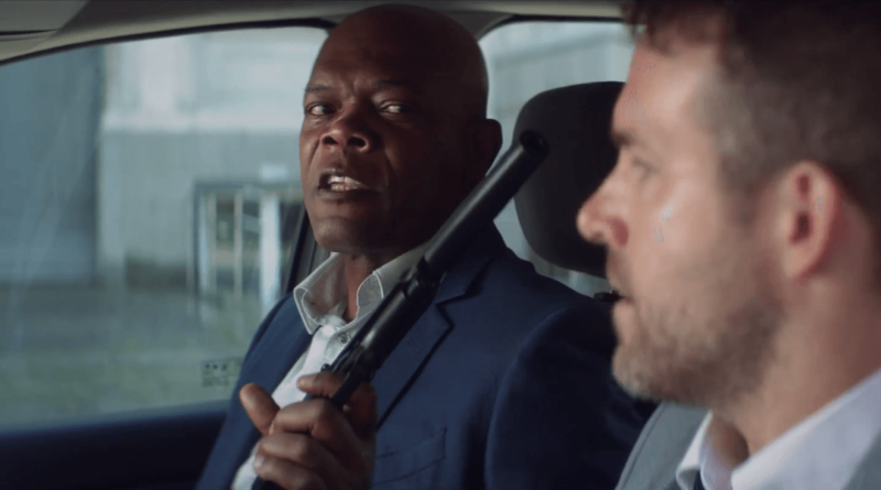 Samuel L. Jackson waving his gun at Ryan Reynolds in THE HITMAN'S BODYGUARD.
